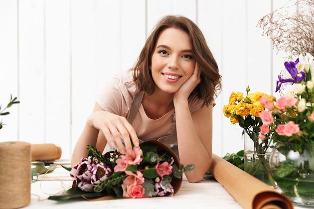 Mujer alegre floreria con flores en el taller