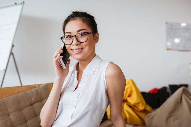Mujer alegre en gafas hablando por teléfono móvil