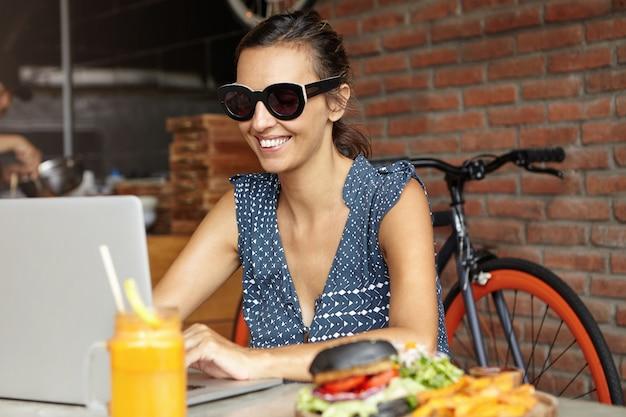 Mujer alegre con gafas de sol modernas comunicándose con un amigo en línea, usando una conexión inalámbrica a internet gratuita en su computadora portátil, sentada en la mesa de café