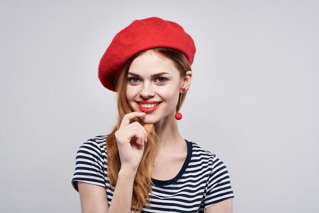 Mujer alegre en un gesto de labios rojos de camiseta a rayas con sus manos fondo aislado