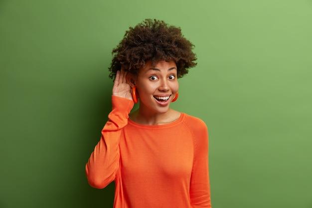 Una mujer alegre y guapa con cabello rizado mantiene la mano cerca de la oreja mientras trata de escuchar una conversación interesante, escucha atentamente a los compañeros de trabajo que hablan en privado, alegres y curiosos, se para en el interior