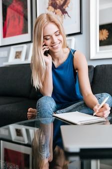 Mujer alegre hablando por teléfono celular y escribiendo en el bloc de notas