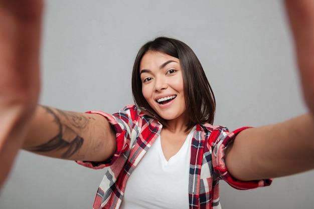 Mujer alegre hacer selfie sobre pared gris.