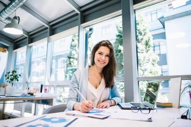 Mujer alegre haciendo papeleo en la computadora portátil