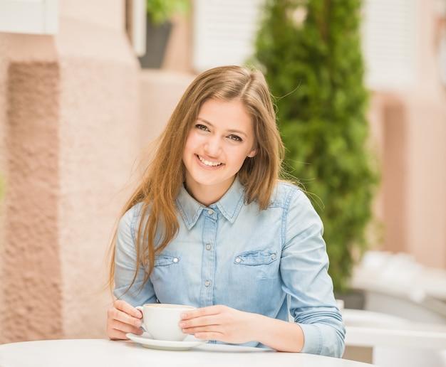 Mujer alegre hermosa que se sienta en café del verano.