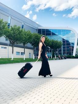 Mujer alegre joven con una maleta. el de viajes y trabajo