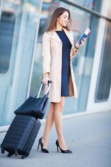 Mujer alegre joven con una maleta.