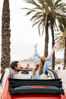 Mujer alegre joven con las manos levantadas y el hombre que se inclina hacia fuera del coche
