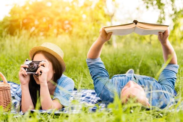 Mujer alegre joven que toma el libro de lectura de la foto y del hombre en hierba