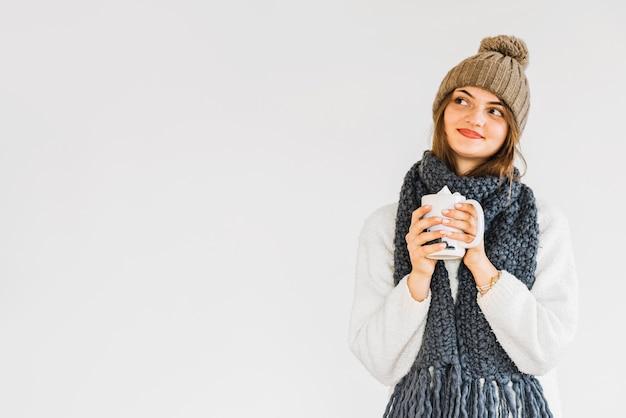 Mujer alegre joven en sombrero y bufanda con la taza de bebida