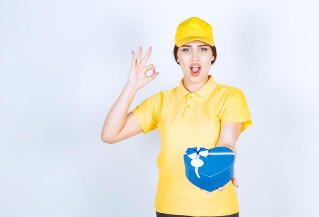 Mujer alegre joven sosteniendo la caja y una mano en forma de corazón y gesticulando con la mano ok