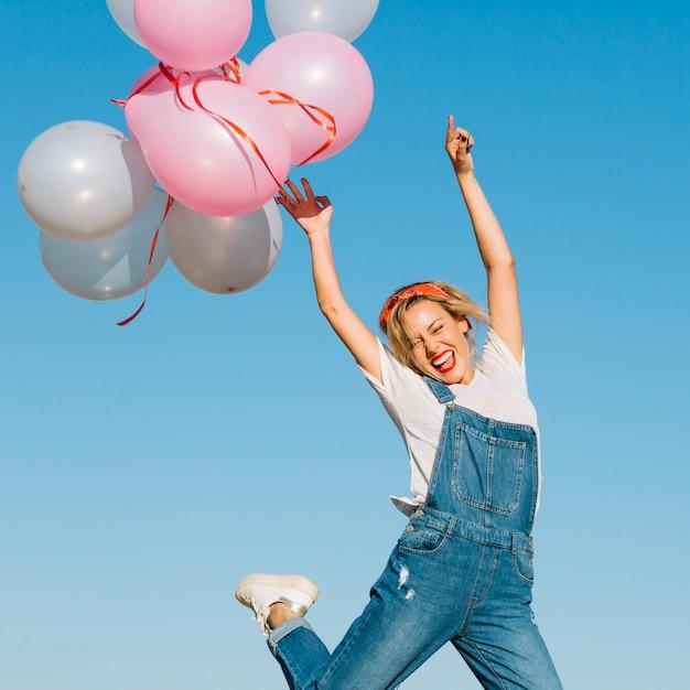 Mujer alegre lanzando globos