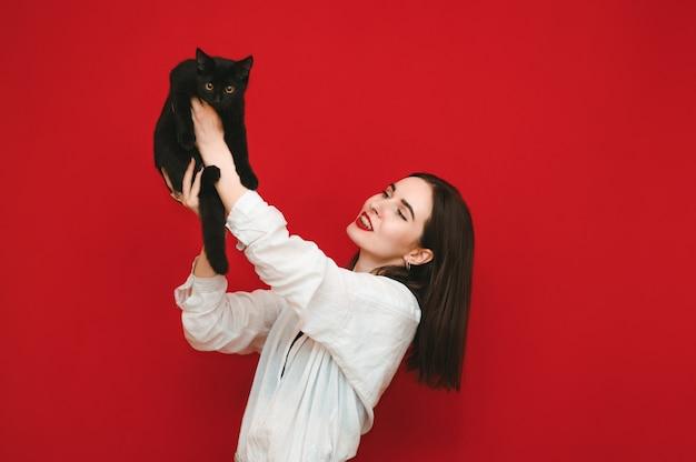Mujer alegre levantó a su gato con las manos en alto
