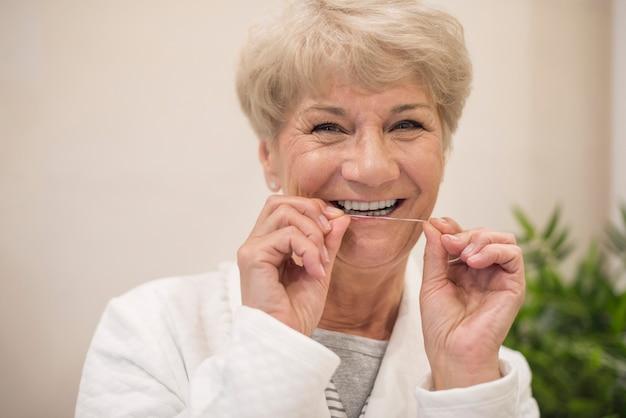 Mujer alegre limpiando sus dientes