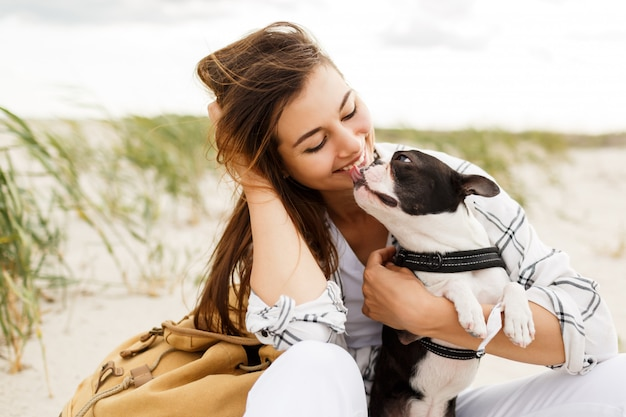 Mujer alegre con lindo perro boston terrier disfrutando de fin de semana cerca del océano.