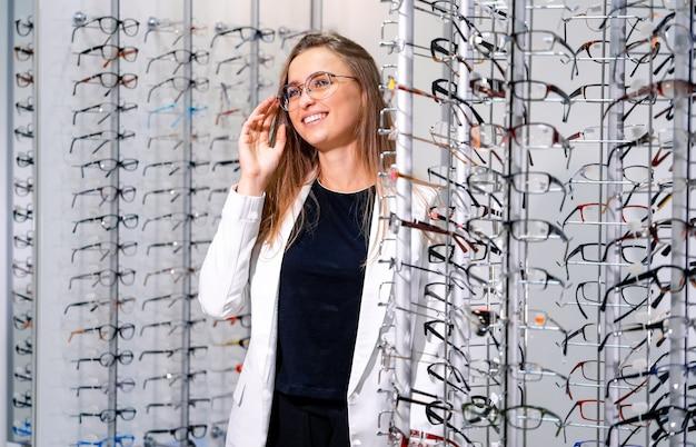Mujer alegre lleva gafas en tienda óptica