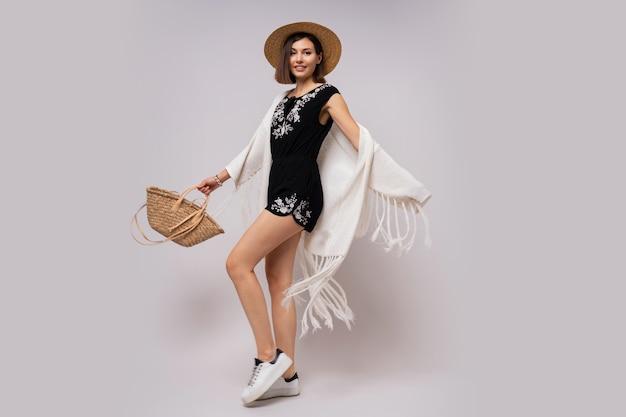 Mujer alegre de longitud completa con peinado corto en elegante traje de verano boho. sombrero de paja y bolso.
