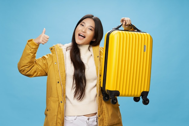 La mujer alegre con una maleta muestra un pulgar