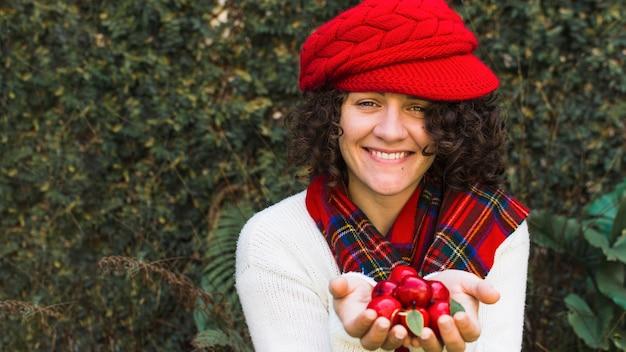 Mujer alegre con manzanas falsas