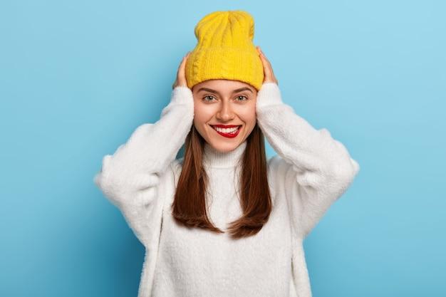 Mujer alegre con maquillaje, lápiz labial rojo brillante, mantiene ambas manos en la cabeza, muestra dientes blancos, usa sombrero y suéter casual