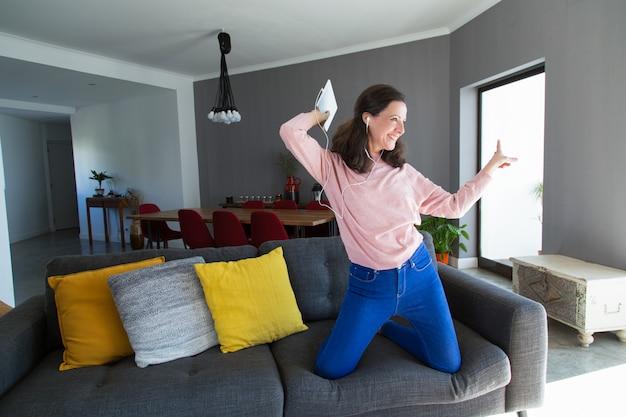 Mujer alegre de mediana edad escuchando música y bailando.