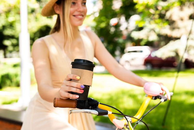 Mujer alegre montando bicicleta con café