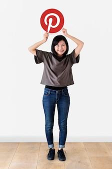 Mujer alegre mostrando un ícono de pinterest