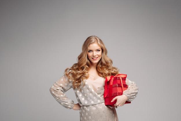 Mujer alegre mujer sosteniendo un montón de cajas con regalos.