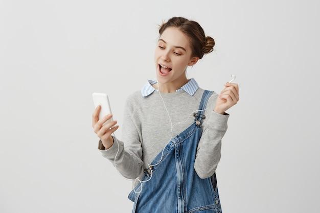 Mujer alegre en overoles casuales utilizando el teléfono móvil para la interacción hablando a través de auriculares. moda mujer blogger facetime con su novio mientras descansa en la cafetería. concepto de relación
