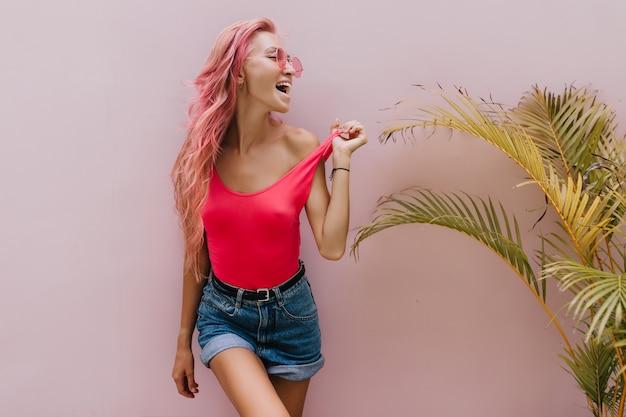 Mujer alegre en pantalones cortos de mezclilla posando junto a la palmera.