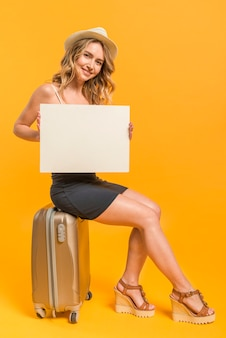 Mujer alegre con papel en blanco sentado en la maleta