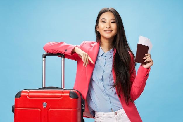 Mujer alegre de pasaporte de apariencia asiática y billete de avión