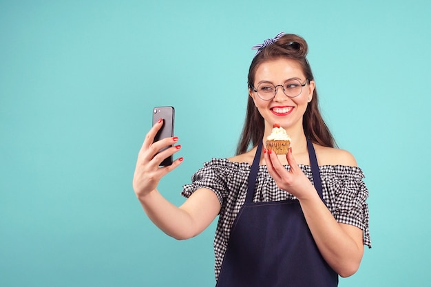 Mujer alegre pastelero hace una selfie con un cupcake en la mano