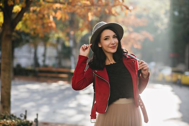 Mujer alegre con pelo negro corto posando en el soleado día de septiembre
