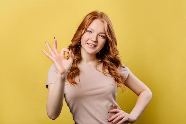 Mujer alegre con el pelo rojo en camiseta guiñando un ojo a la cámara y mostrando un signo bien, aislado