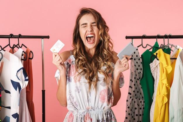 Mujer alegre de pie cerca del armario mientras sostiene el teléfono inteligente y la tarjeta de crédito aislado en rosa