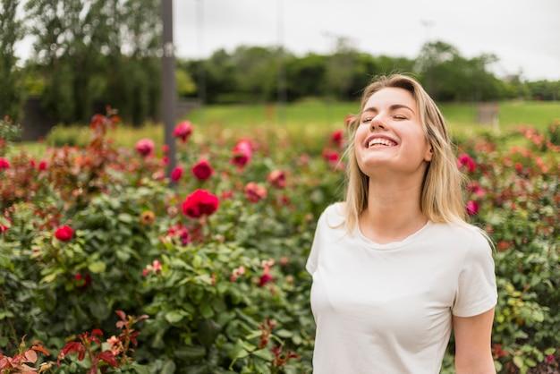 Mujer alegre de pie en el jardín de flores