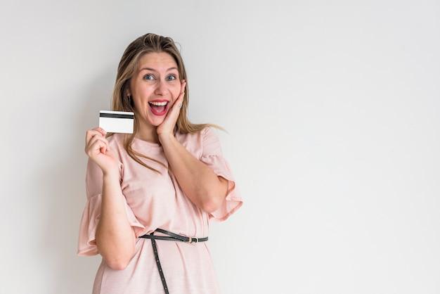 Mujer alegre de pie con tarjeta de crédito