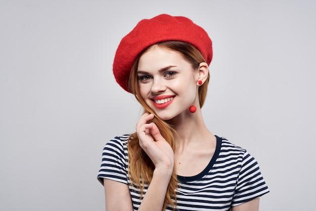 Mujer alegre posando moda mirada atractiva pendientes rojos joyería fondo claro