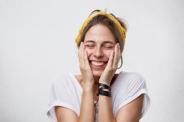 Mujer alegre positiva sosteniendo sus manos en las mejillas sonriendo ampliamente cerrando los ojos con placer de buen humor
