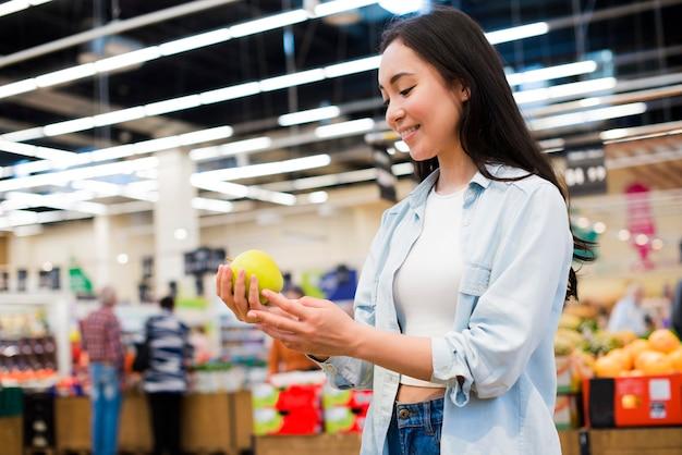 Mujer alegre que comprueba la manzana en tienda de comestibles