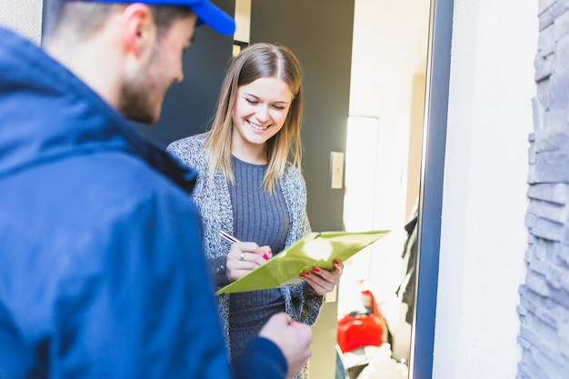 Mujer alegre que firma el papel después de la entrega