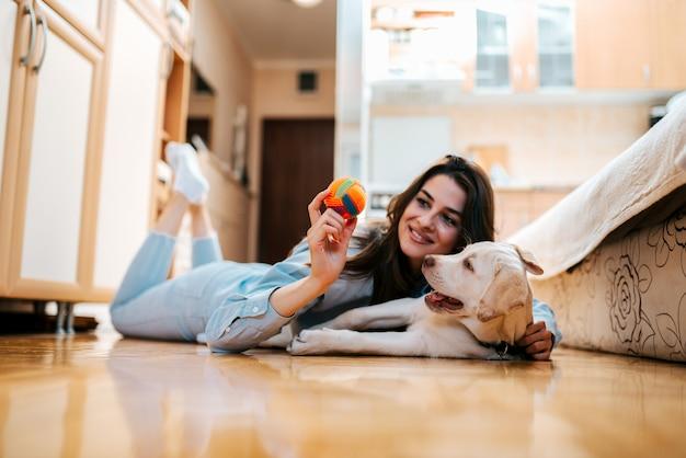 Mujer alegre que juega con su perro en el apartamento.