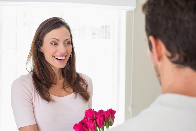 Mujer alegre que mira al hombre con las flores