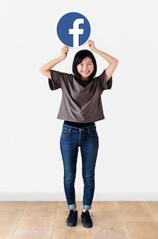 Mujer alegre que muestra un icono de facebook