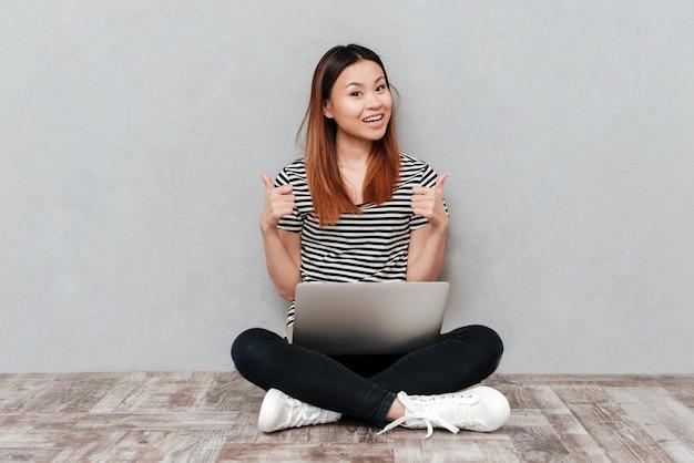Mujer alegre que muestra los pulgares para arriba mientras trabajaba con la computadora portátil
