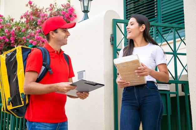 Mujer alegre que recibe el paquete de mensajería y sonriendo. repartidor feliz con mochila térmica amarilla vistiendo uniforme rojo y hablando con la clienta. servicio de entrega a domicilio y concepto de correo.