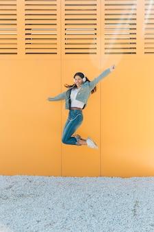 Mujer alegre que salta contra la pared estirando sus brazos