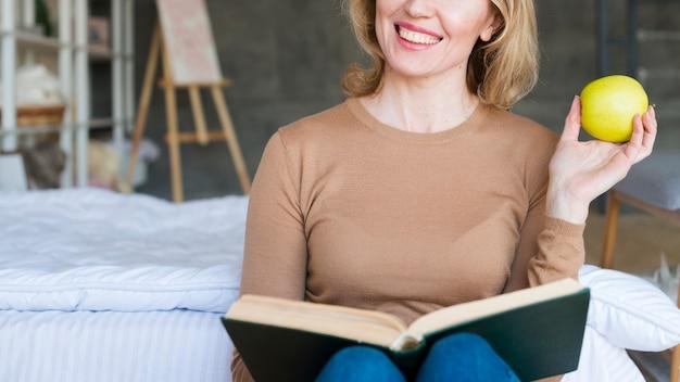 Mujer alegre que se sienta con el libro y la manzana