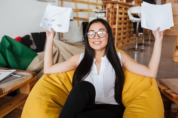 Mujer alegre que se sienta en la silla del puf y que sostiene los papeles